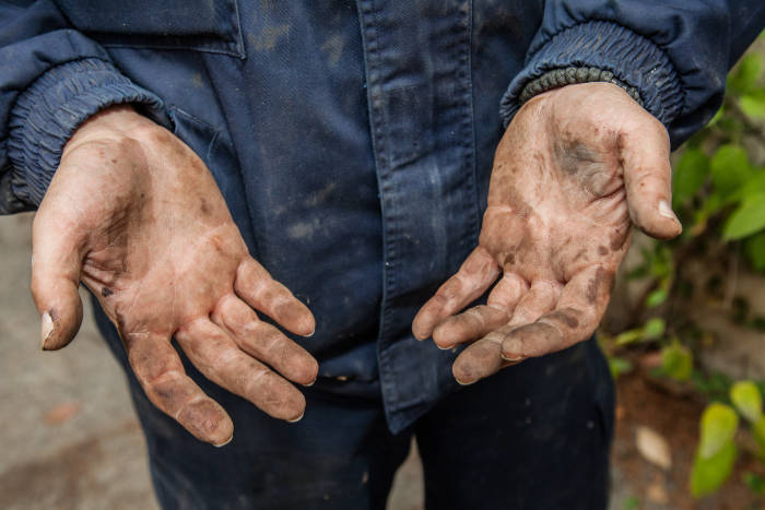 Hands Of A Mechanic Soiled By Engine Oil